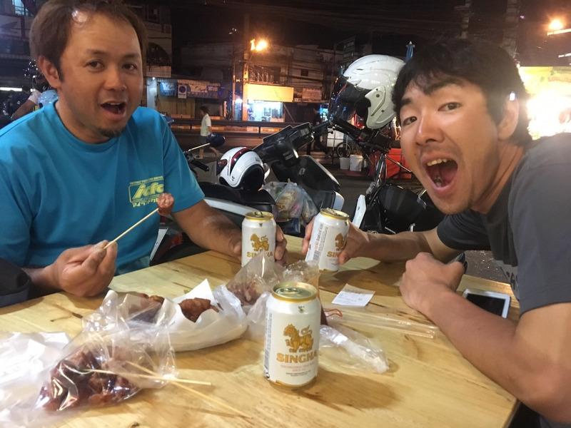 タイの市場で唐揚げをつまみながらシンハービールを飲む遠藤社長と須江