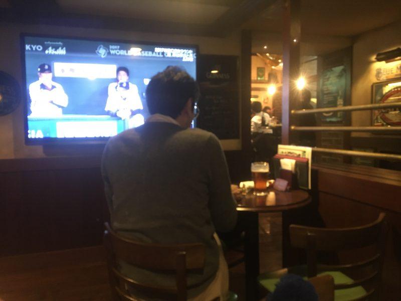 スポーツバーで一人飲むオジサンを後ろから撮影する須江